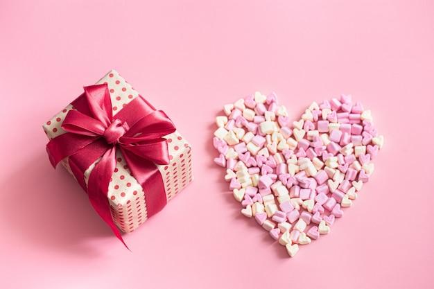 Il concetto di san valentino. confezione regalo con fiocco rosso su rosa. Foto Gratuite