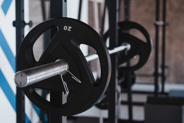 Представление о силе. черная штанга на металлической подставке в спортзале в дневное время. нет людей вокруг Бесплатные Фотографии