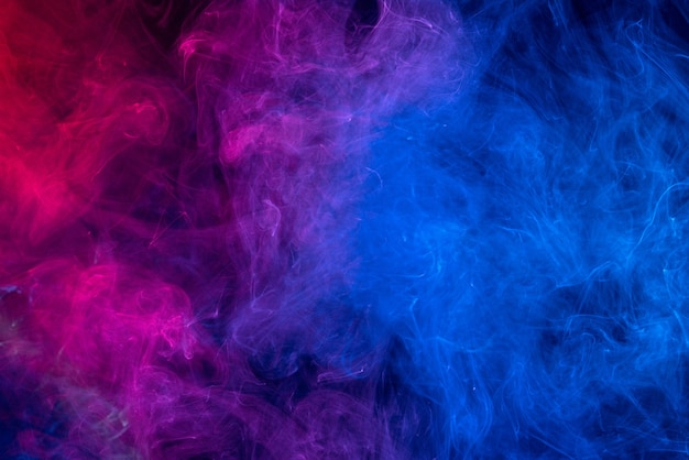 Conceptual image of colorful red and blue color smoke isolated on dark black background, halloween concept design element. Premium Photo