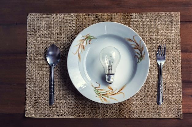 The conceptual image depicts the eating of ideas. and innovation with a dining set Premium Photo