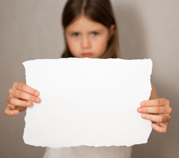 悲しい落胆した少女の概念図は灰色の背景に白紙を保持 Premium写真
