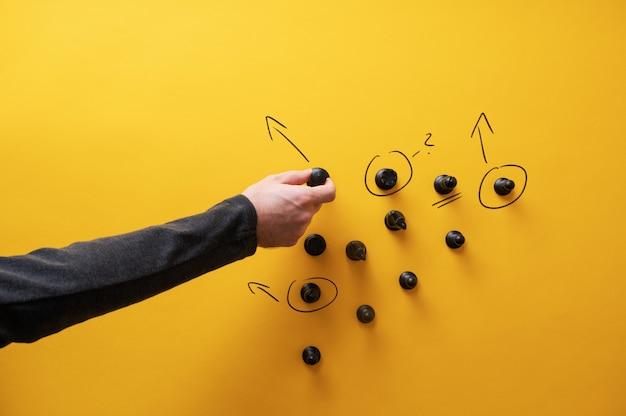 戦略的計画の概念的なイメージ-チェスの駒の周りに矢印と疑問符を描く男性の手描き。 Premium写真