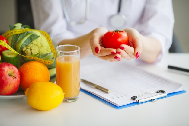 Conceptual photo of a female nutritionist with fruits on the desk Premium Photo