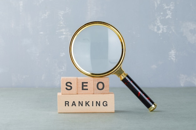 Conceptual of seo analysis and business. with wooden blocks with words on it, magnifying glass side view. Free Photo