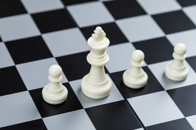 Conceptual of strategy and chess. on checkerboard surface high angle view. horizontal image Free Photo