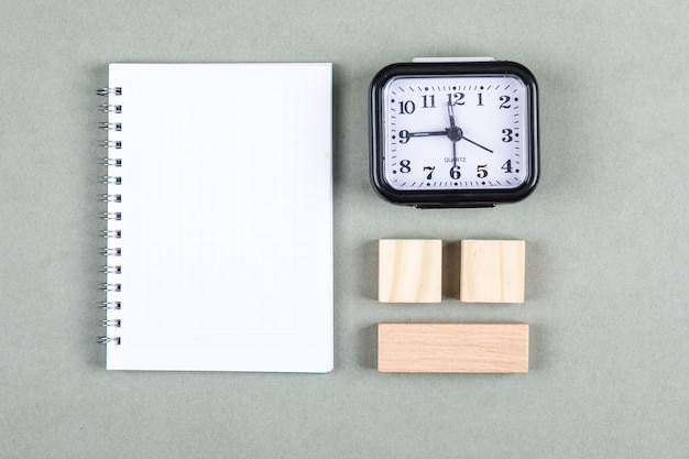 Conceptual of time management and brainstorming. with clock, notebook, wooden blocks on gray background top view. horizontal image Free Photo