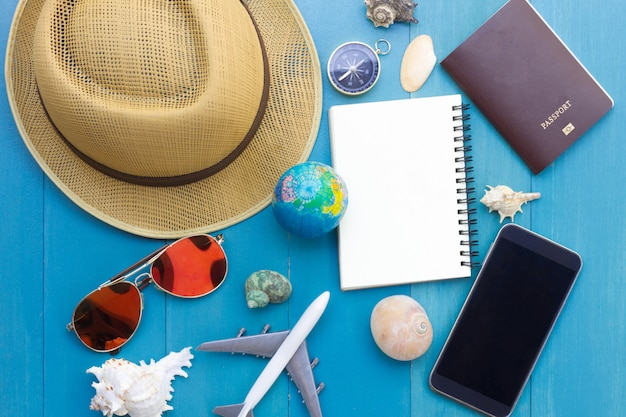 Conceptual tour planing image of travelling accessories on blue wooden background Premium Photo