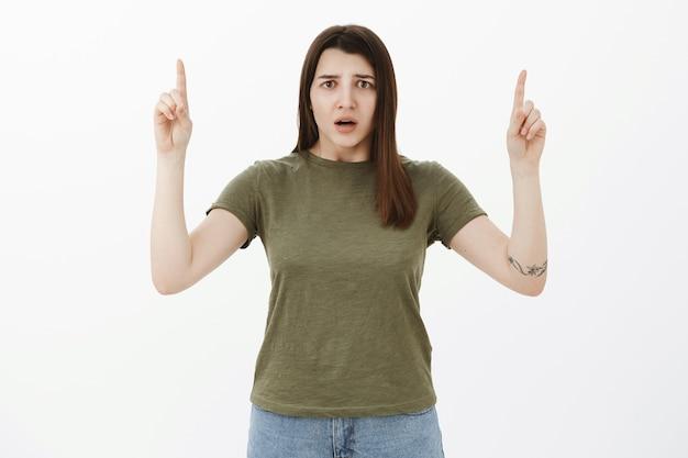 心配して混乱している悲しい少女は、灰色の壁の上に上げられた手で上を向いているように神経質に見ている欲求不満とショックで顔をしかめた開口部に何が起こったのか理解できません。 無料写真