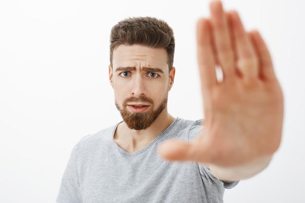 Обеспокоенный и встревоженный красивый молодой друг-мужчина с голубыми глазами, бородой и усами тянет ладонь к себе, чтобы предупредить и перестать делать неправильный выбор. Бесплатные Фотографии