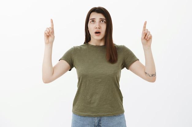 心配して心配している20代の若い女性を指して、口を開けて心配そうに見ている、木に上向きの子猫の神経の安全性 無料写真