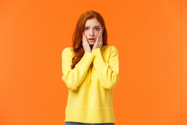 Concerned and anxious redhead girl grabs her face, gasping scared and troubled, dont know what do, standing tensed and afraid, Premium Photo