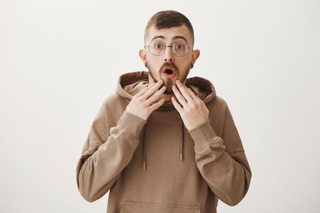 Ragazzo preoccupato con gli occhiali che guarda con preoccupazione Foto Gratuite