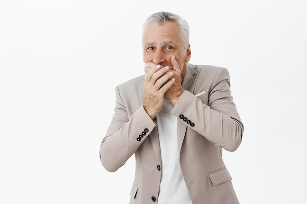 Concerned and shocked senior man cover mouth with hands and looking worried Free Photo