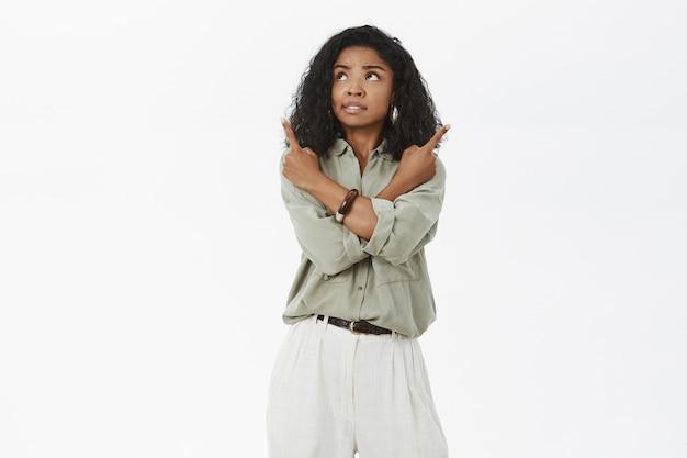 Donna adulta afroamericana attraente travagliata interessata con l'acconciatura riccia che si sente incerta incrocio le braccia sul corpo e punta in direzioni diverse Foto Gratuite