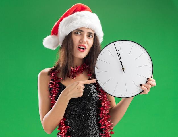 Giovane bella ragazza interessata che indossa il cappello di natale con la ghirlanda sulla tenuta del collo e indica l'orologio da parete isolato sulla parete verde Foto Gratuite