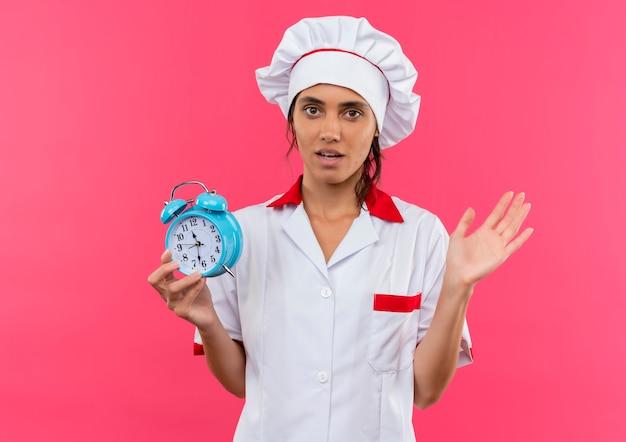 La giovane donna preoccupata che indossa la sveglia uniforme della tenuta del cuoco unico ha diffuso la mano sulla parete rosa isolata con lo spazio della copia Foto Gratuite