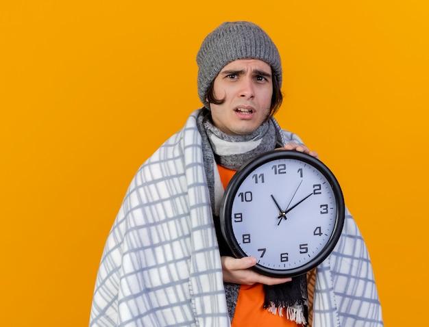 オレンジ色で隔離の壁時計を保持している格子縞に包まれたスカーフと冬の帽子をかぶっている心配している若い病気の人 無料写真