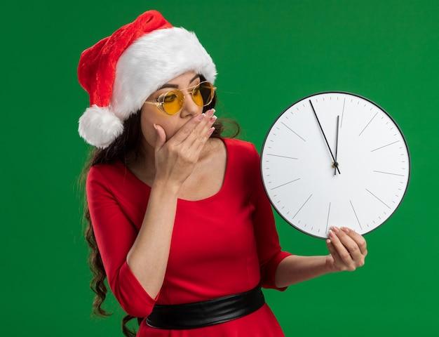Interessato giovane bella ragazza che indossa santa cappello e occhiali tenendo e guardando l'orologio tenendo la mano sulla bocca isolato su sfondo verde Foto Gratuite