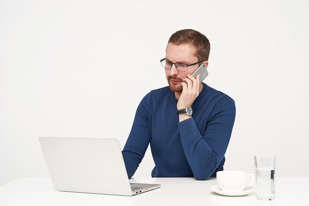 Preoccupato giovane imprenditore dai capelli biondi non rasati in vetri che effettua chiamate con il suo smartphone mentre si lavora su sfondo bianco in abiti casual Foto Gratuite