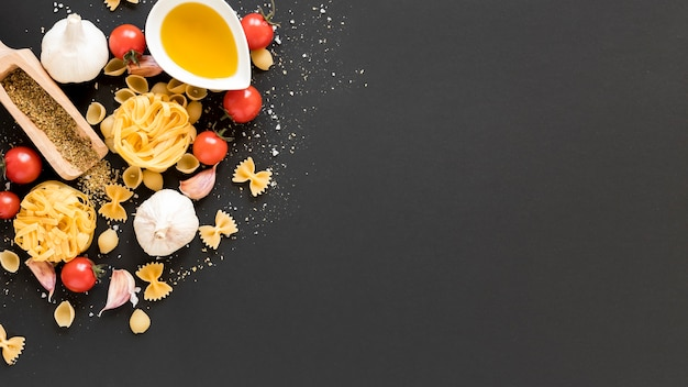 タリアテッレと原料。 conchiclioni;タリアテッレファルファッレ黒の背景上の油 無料写真