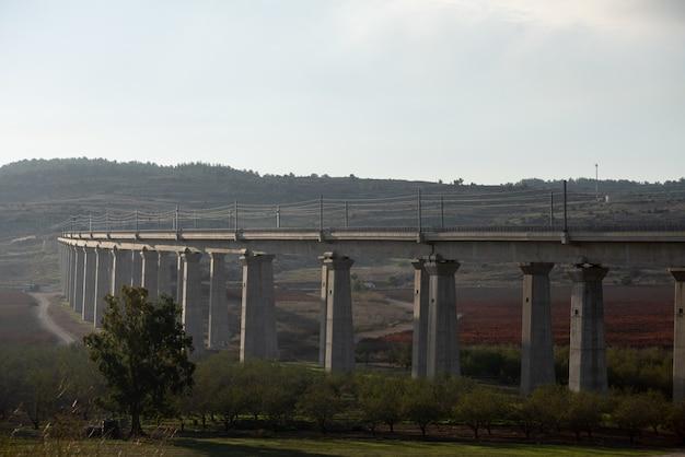 Бетонный мост в поле, окруженном зеленью с холмами на заднем плане Бесплатные Фотографии