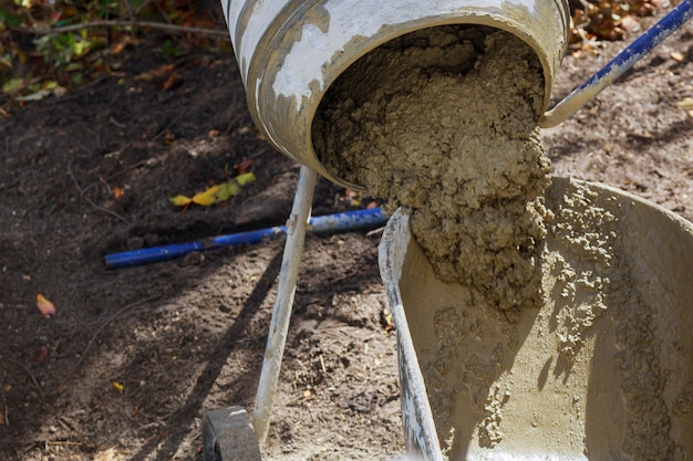 An concrete mixer poured the finished solution into a bucket Premium Photo