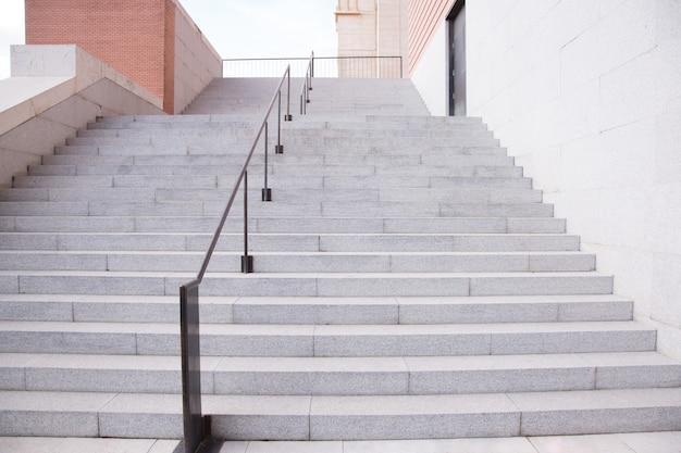 Бетонная лестница и перила с кирпичной стеной наверху в жилом доме строительной индустрии. лестница внутренняя наружная. Premium Фотографии