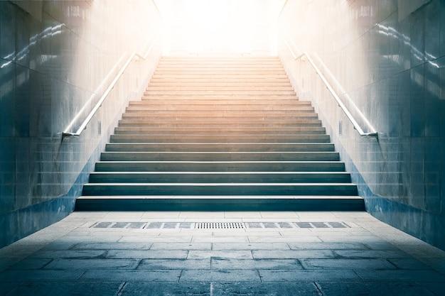 빛을 향해 이어지는 콘크리트 계단. 희망과 밝은 미래의 개념. 프리미엄 사진