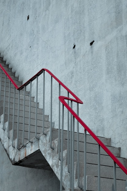 Concrete stairs with a red handrail Free Photo