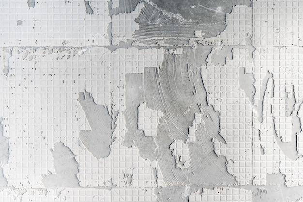 改修前にタイルを取り外した後の硬い接着剤石膏パターン表面へのコンクリート壁のテクスチャ。リフォーム・リフォーム事業。 Premium写真