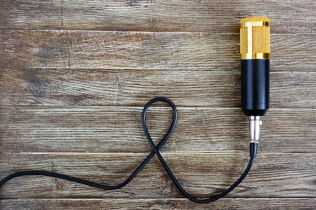 Condenser gold microphone with cable lies on a wooden table with copy space. musical theme. flat lay. top view. Premium Photo