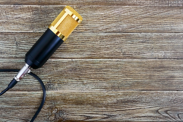 Condenser gold microphone with cable on a wooden table with copy space. musical theme. flat lay. top view. Premium Photo