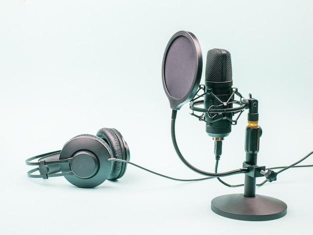 콘덴서 마이크와 파란색 배경에 유선 헤드폰. 사운드 녹음 및 재생 용 장비. 프리미엄 사진
