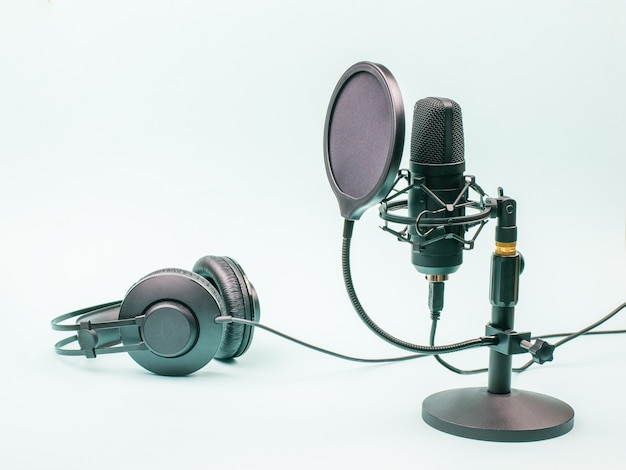 Condenser microphone and wired headphones on a blue background. equipment for recording and reproducing sound. Premium Photo