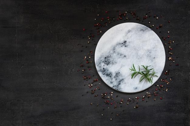 Condiments and spices on round stone board. Premium Photo