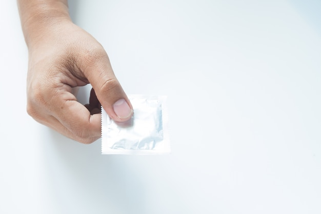Condom in male hand on white background Free Photo
