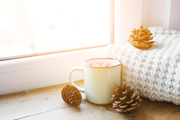 Cones and hot chocolate near scarf and window Free Photo