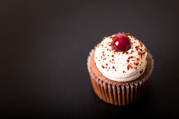 Confection dessert homemade black forest cupcake on a black slate stone plate Premium Photo