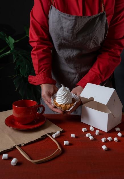 赤いテーブルの近くに白いケーキと白い紙箱を保持している菓子屋 Premium写真