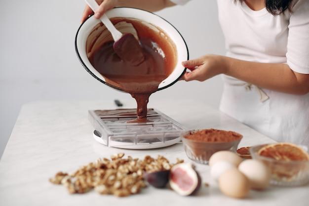 お菓子屋さんが具材を混ぜます。女性がデザートを準備しています。女性がケーキを焼きます。 無料写真