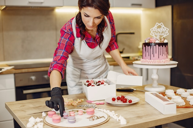 Confectioner in a uniform decorates the cakes Free Photo
