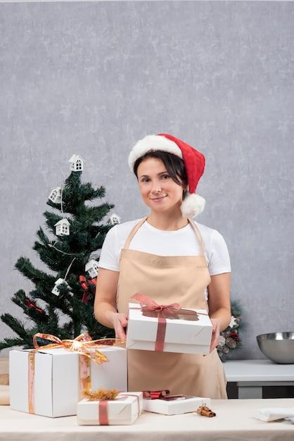 앞치마에 제과 여자는 과자 선물 상자를 보유하고 있습니다. 휴가. 수직 프레임 프리미엄 사진