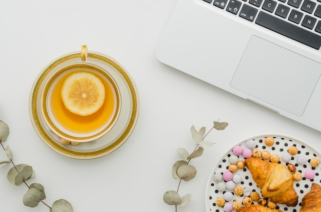 Confectionery and croissant on plate with lemon tea near the open laptop on white background Free Photo