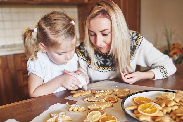 クリスマスクッキーを飾る女性の手で製菓職場。ホームベーカリー、日当たりの良い甘い冬休み。 無料写真