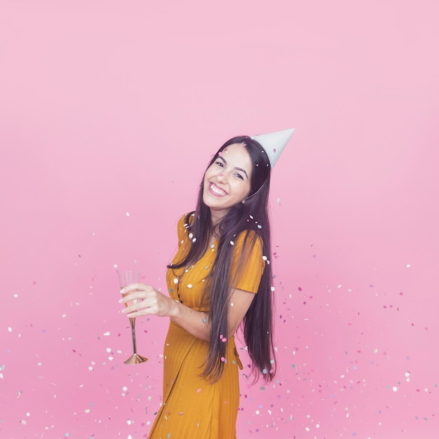 Confetti falling over the smiling young woman holding champagne flute Free Photo