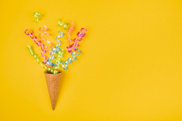 Confetti in ice-cream cone with copy-space on yellow background Free Photo