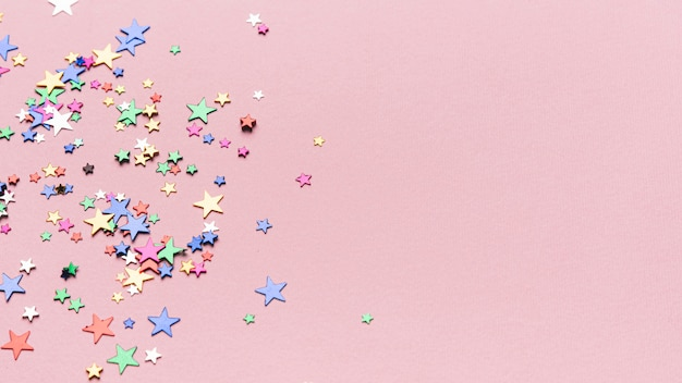 Confetti stars on pink background with copy space Free Photo