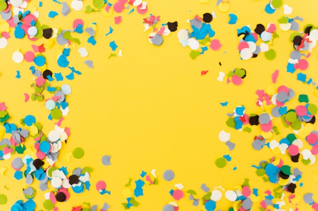 Confetti on yellow background after finishing the party Free Photo