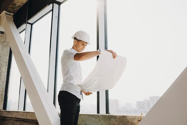 큰 창 근처 건설에서 건물의 계획을보고 자신감 성인 Arhitect. 프리미엄 사진