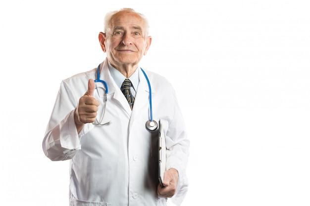 Уверенно и красивый усмехаясь старший доктор или профессор при стетоскоп и папка документов показывая большие пальцы руки вверх изолированные на белизне Premium Фотографии